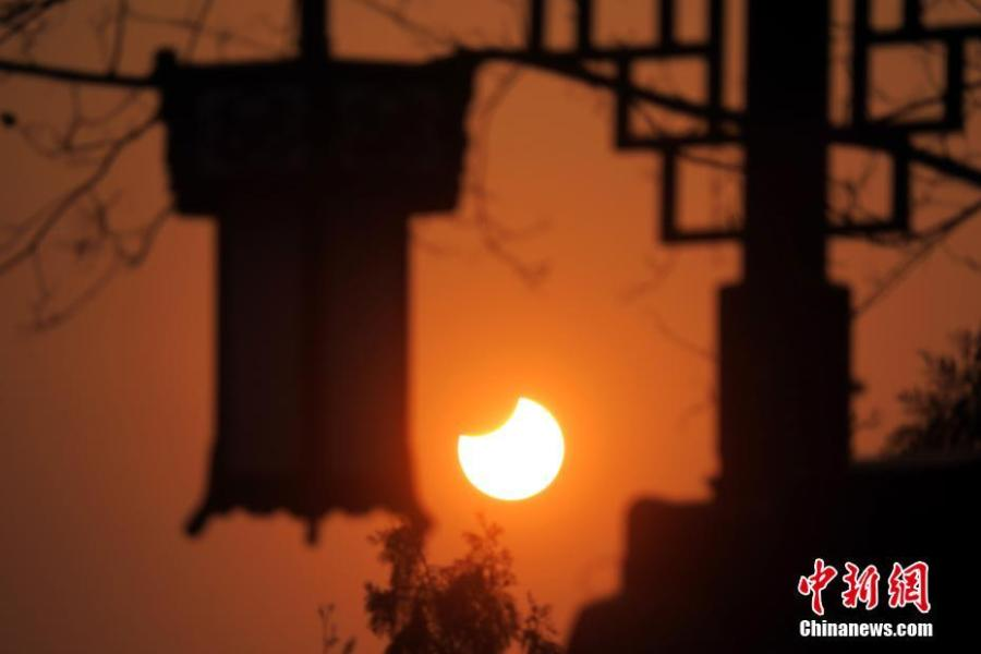 A partial solar eclipse is observed next to lanterns in Jingshan Park in Beijing, Jan. 6, 2019. (Photo: China News Service/Sun Zifa)