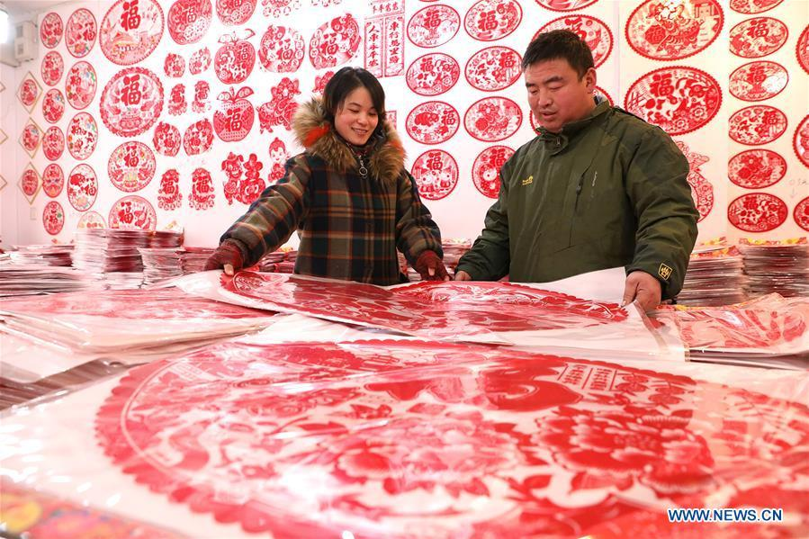 A customer (R) selects New Year goods at a market in Shijiazhuang, north China\'s Hebei Province, Jan. 6, 2019. People are busy buying decorations such as Spring Festival couplets and lanterns to greet the upcoming Lunar New Year. (Xinhua/Liang Zidong)