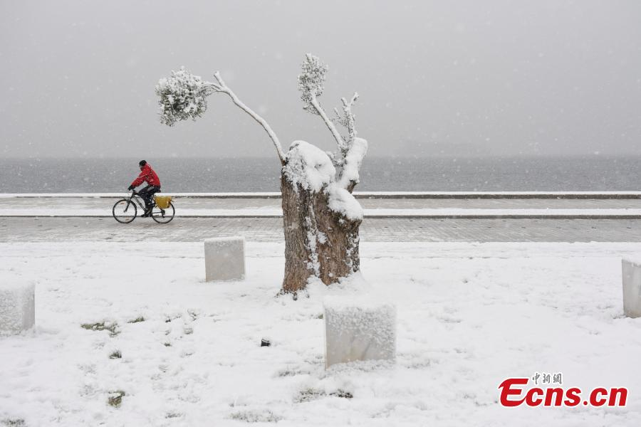A man rides his bike during snowfall at the seaside promenade of Thessaloniki, Greece, Jan. 4, 2019. An elderly woman was found dead and two men were missing after blizzards hit parts of Greece, police officials said on Saturday. (Photo/Agencies)