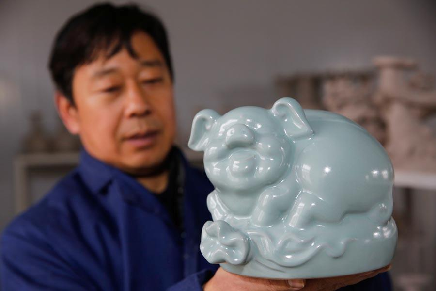 A Ru porcelain pig is shown at the studio of Wang Guoqi in Baofeng county, Pingdingshan city, Central China\'s Henan Province, Jan. 7, 2019. Pig-themed porcelain works are being made there as New Year mascots to welcome the upcoming Year of the Pig in the lunar Chinese calendar. The lunar New Year falls on Feb 5 this year. (Photo/Asianewsphoto)