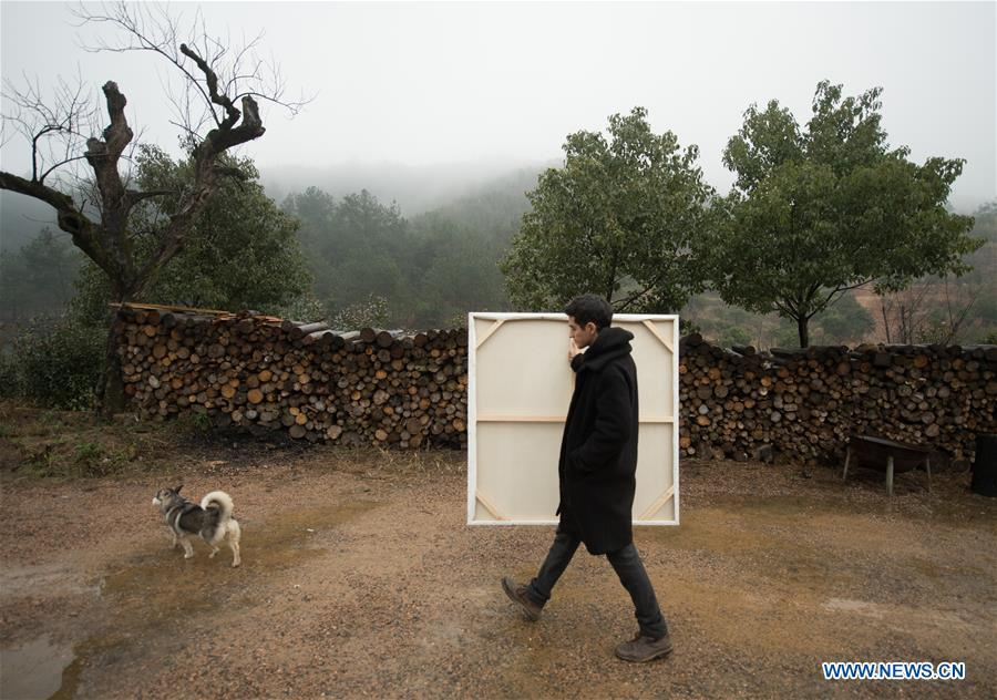 Mehraz Karami carries a painting at Shanbei Village in Daixi Town of Huzhou City, east China\'s Zhejiang Province, Jan. 7, 2019. Iranian Mehraz Karami, who was born in Tehran in 1993, has shown his interest in Chinese culture ever since his childhood. He came to Daixi Town and set up his own painting workshop at the end of 2017 after graduation from east China\'s Shanghai. He said he hoped to stay in China and become an artist. (Xinhua/Weng Xinyang)