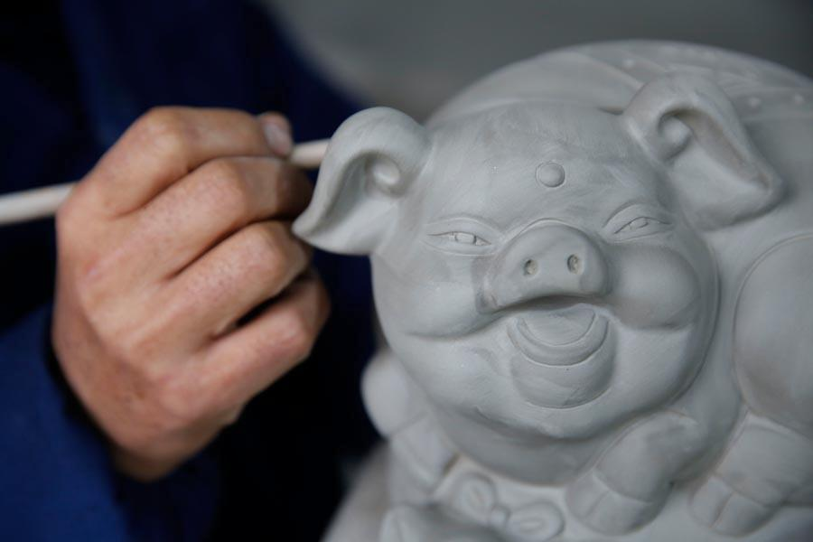 Wang Guoqi works on the base of a Ru porcelain ware shaped like a pig at his studio in Central China\'s Henan Province on Jan. 7, 2019. (Photo/Asianewsphoto)