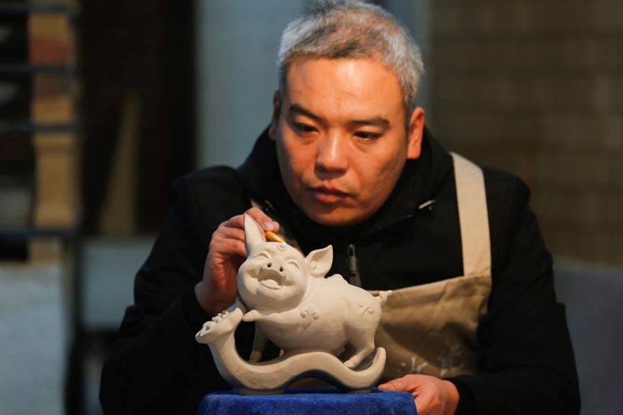 A man works on the base of a Ru porcelain ware shaped like a pig at Wang Guoqi\'s studio in Central China\'s Henan Province on Jan. 7, 2019. (Photo/Asianewsphoto)