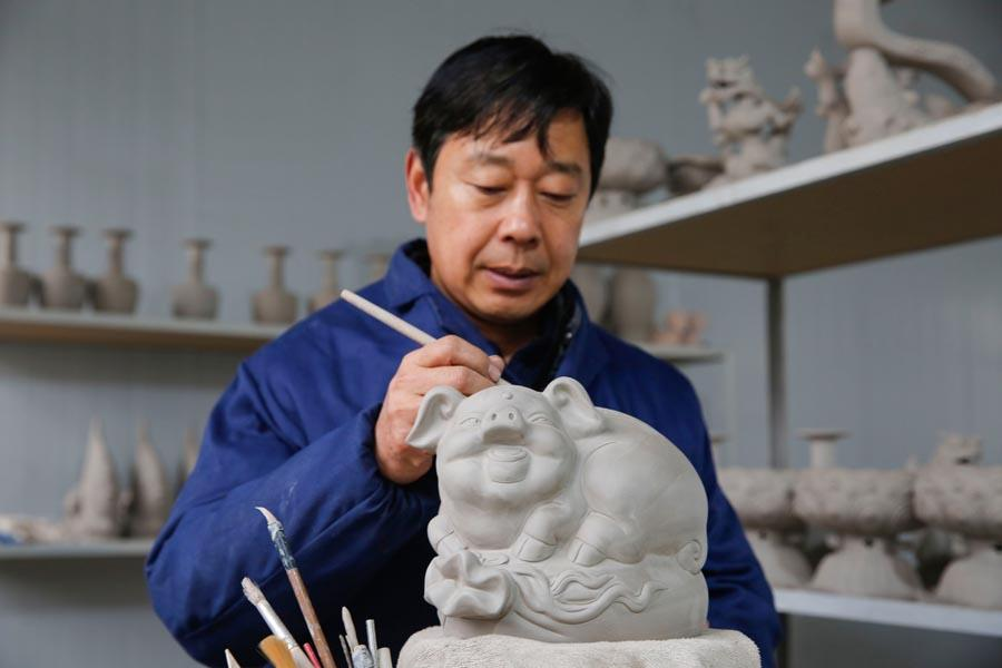 Craftsman Wang Guoqi works on the base of a Ru porcelain pig in Baofeng county, Pingdingshan city, Central China\'s Henan Province, Jan. 7, 2019. Wang is an inheritor of Ru porcelain, one of China\'s \