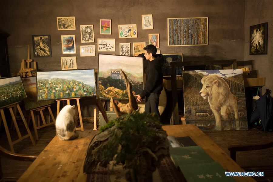 Mehraz Karami arranges paintings at his workshop in Shanbei Village of Daixi Town in Huzhou City, east China\'s Zhejiang Province, Jan. 7, 2019. Iranian Mehraz Karami, who was born in Tehran in 1993, has shown his interest in Chinese culture ever since his childhood. He came to Daixi Town and set up his own painting workshop at the end of 2017 after graduation from east China\'s Shanghai. He said he hoped to stay in China and become an artist. (Xinhua/Weng Xinyang)