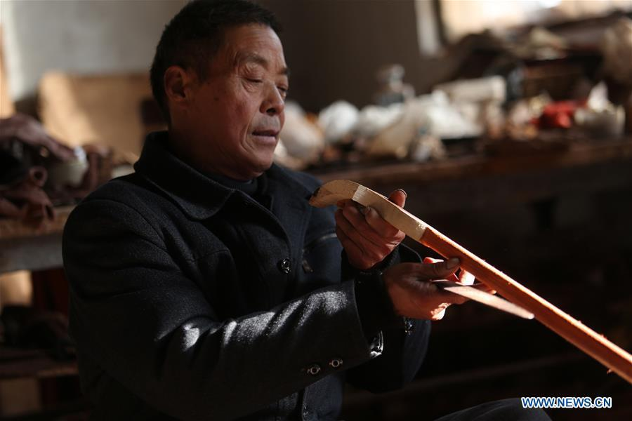 Villager Gao Zhenbao checks the pole of Erhu, a Chinese two-stringed bowed instrument at Yuequan Village of Miaoshan Town in Linyi City, east China\'s Shandong Province, Jan. 8, 2019. Yuequan is famous for its time-honored handmade Erhu, with more than 90 households dedicated to it in the village. (Xinhua/Zhang Chunlei)