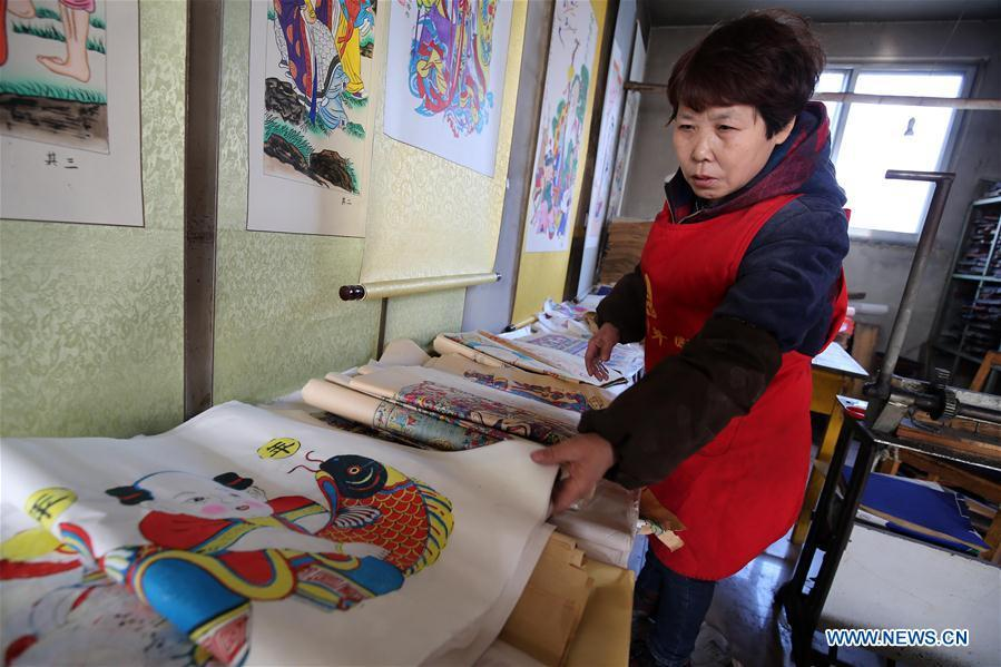 A folk artist arranges woodblock New Year paintings in Yangjiabu Village of Hanting District in Weifang, east China\'s Shandong Province, Jan. 8, 2019. Local folk artists are busy making woodblock New Year paintings for the upcoming Spring Festival, which starts from the first day of the first month of the Chinese lunar calendar, or Feb. 5 this year. (Xinhua/Zhang Chi)