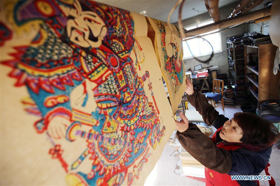 A folk artist airs woodblock New Year paintings in Yangjiabu Village of Hanting District in Weifang, east China\'s Shandong Province, Jan. 8, 2019. Local folk artists are busy making woodblock New Year paintings for the upcoming Spring Festival, which starts from the first day of the first month of the Chinese lunar calendar, or Feb. 5 this year. (Xinhua/Zhang Chi)