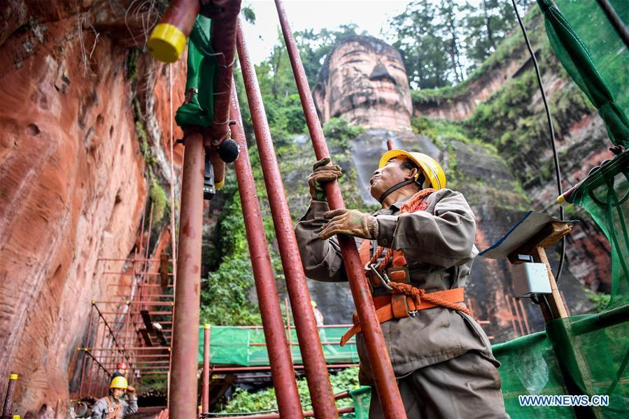 Workers install scaffolds for the examination work of the Leshan Giant Buddha in Leshan City, southwest China\'s Sichuan Province, Oct. 19, 2018. The National Cultural Heritage Administration will work out a plan to better protect cultural relics and speed up the creation of a safety oversight platform in 2019. Stressing the importance of such protection, Liu Yuzhu, head of the administration, said lax enforcement is a prominent problem that endangers cultural relics, at a meeting attended by cultural heritage administrators nationwide. (Xinhua/Zhang Chaoqun)