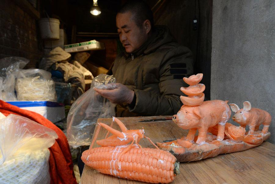 Sculptures carved out of carrots by Guo Yuhong, a Hebei vegetable vendor.  (Photo by Hao Qunying for chinadaily.com.cn)