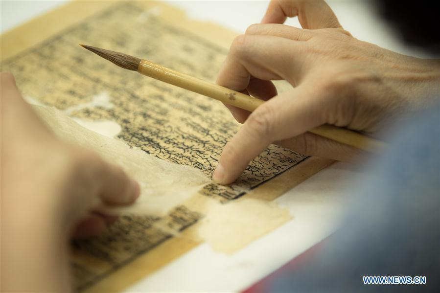 Yan Jingshu restores an ancient book at Zhejiang Library in Hangzhou, east China\'s Zhejiang Province, May 23, 2018. The National Cultural Heritage Administration will work out a plan to better protect cultural relics and speed up the creation of a safety oversight platform in 2019. Stressing the importance of such protection, Liu Yuzhu, head of the administration, said lax enforcement is a prominent problem that endangers cultural relics, at a meeting attended by cultural heritage administrators nationwide. (Xinhua/Weng Xinyang)