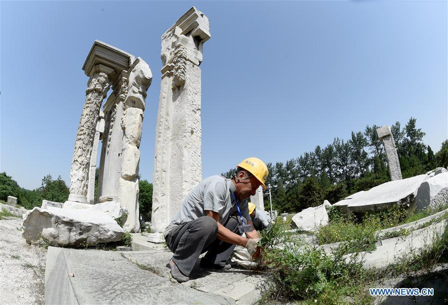 Staff members clean up weeds at ruins of Yuanying Guan (Immense Ocean Observatory) at Yuanmingyuan in Beijing, capital of China, May 23, 2018. The National Cultural Heritage Administration will work out a plan to better protect cultural relics and speed up the creation of a safety oversight platform in 2019. Stressing the importance of such protection, Liu Yuzhu, head of the administration, said lax enforcement is a prominent problem that endangers cultural relics, at a meeting attended by cultural heritage administrators nationwide. (Xinhua/Luo Xiaoguang)