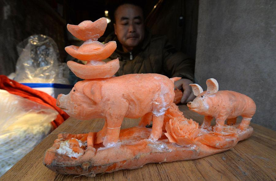 A sculpture of pigs carved out of carrots by Guo Yuhong, a vegetable vendor at a market in Handan, North China\'s Hebei Province.  (Photo by Hao Qunying for chinadaily.com.cn)