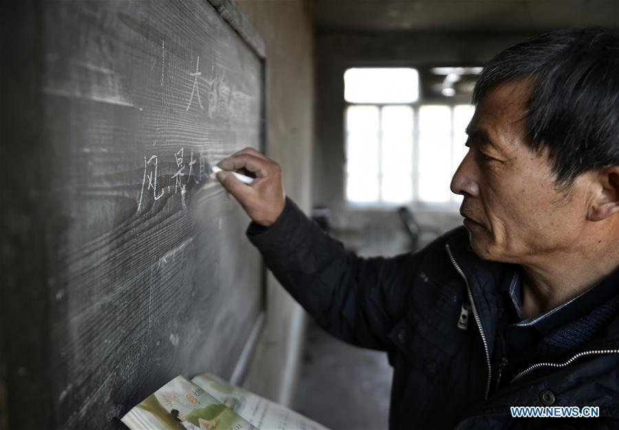 Hu Zhisheng writes on the blackboard at Yantai primary school in Yantai Village of Lianhua Township in Tieling City, northeast China\'s Liaoning Province, Jan. 7, 2019. Located in a remote mountain village, most students of Yantai school had transferred to other places outside the mountain. Sun Xiaofeng, a third grade student, became the only student of the school in September last year taught by Hu Zhisheng, the only one faculty of Yantai primary school. (Xinhua/Yao Jianfeng)