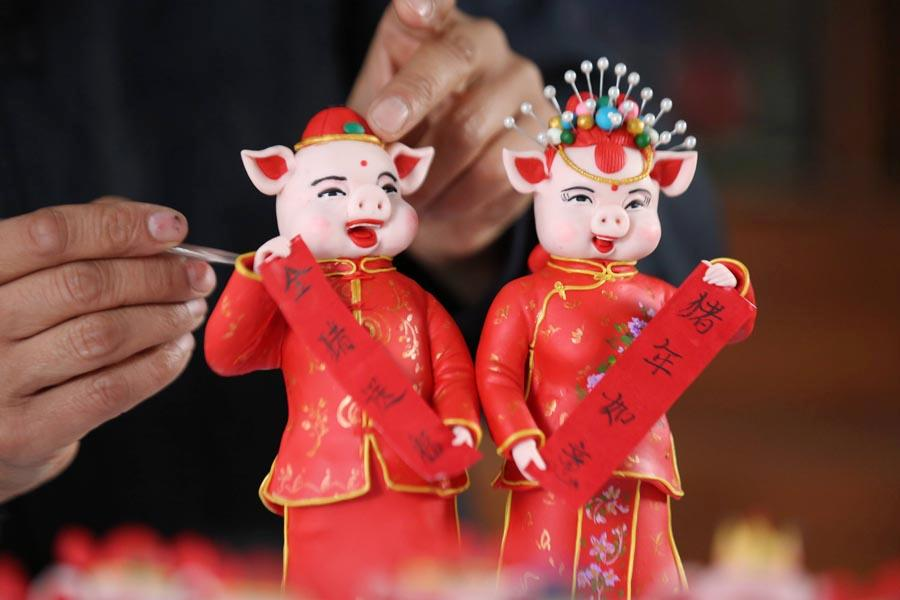 Chinese people expect loads of pig-themed decorations and items as the lunar Year of the Pig draws near. This photo taken on Jan. 8, 2019 shows a pair of dough figurines of pigs holding couplets to greet people for an auspicious new year. They were made by craftsman Zuo Ansheng in Linyi city in East China\'s Shandong Province. (Photo/Asianewsphoto)