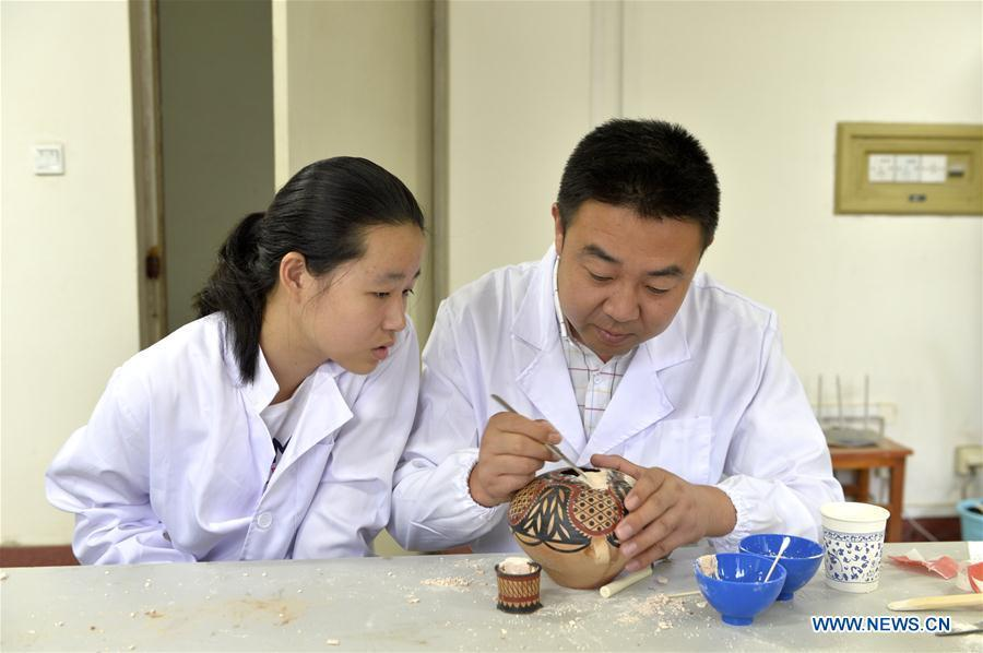 A staff member teaches a girl to repair colored pottery at Gansu Museum in Lanzhou, northwest China\'s Gansu Province, Aug. 16, 2018. The National Cultural Heritage Administration will work out a plan to better protect cultural relics and speed up the creation of a safety oversight platform in 2019. Stressing the importance of such protection, Liu Yuzhu, head of the administration, said lax enforcement is a prominent problem that endangers cultural relics, at a meeting attended by cultural heritage administrators nationwide. (Xinhua/Li Xiao)