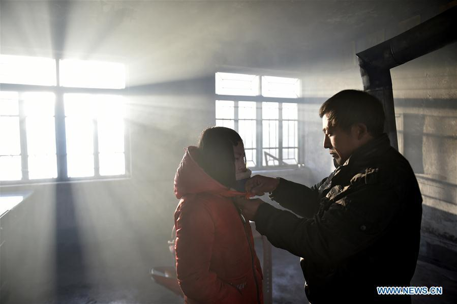Hu Zhisheng helps his student Sun Xiaofeng to tie the red scarf in Yantai Village of Lianhua Township in Tieling City, northeast China\'s Liaoning Province, Jan. 8, 2019. Located in a remote mountain village, most students of Yantai school had transferred to other places outside the mountain. Sun Xiaofeng, a third grade student, became the only student of the school in September last year taught by Hu Zhisheng, the only one faculty of Yantai primary school. (Xinhua/Yao Jianfeng)