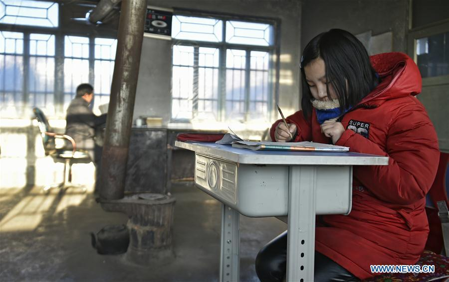 Sun Xiaofeng answers exercises at Yantai primary school in Yantai Village of Lianhua Township in Tieling City, northeast China\'s Liaoning Province, Jan. 8, 2019. Located in a remote mountain village, most students of Yantai school had transferred to other places outside the mountain. Sun Xiaofeng, a third grade student, became the only student of the school in September last year taught by Hu Zhisheng, the only one faculty of Yantai primary school. (Xinhua/Yao Jianfeng)