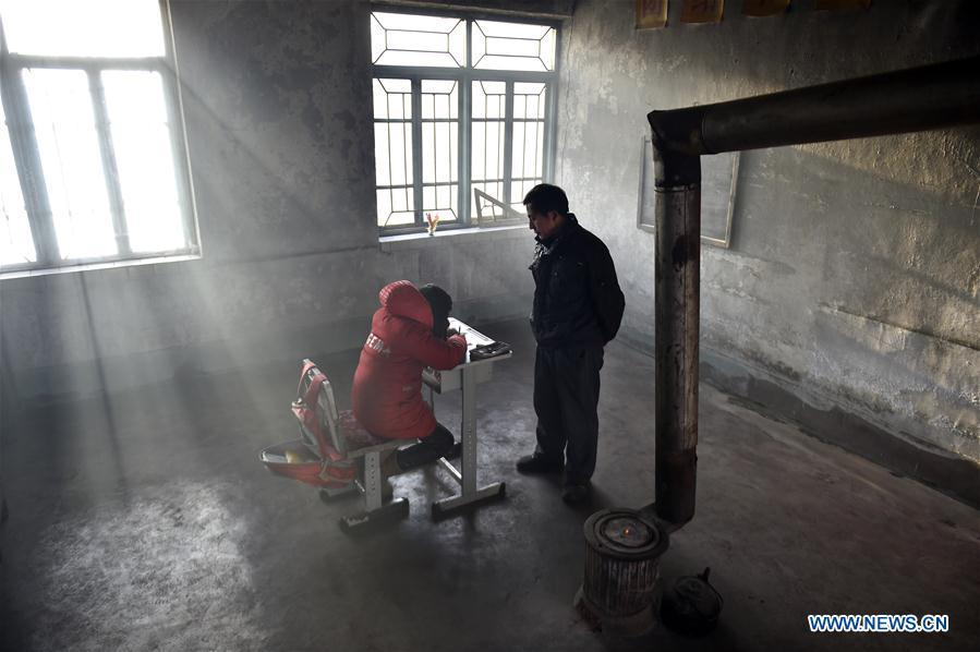 Hu Zhisheng tutors his student Sun Xiaofeng at Yantai primary school in Yantai Village of Lianhua Township in Tieling City, northeast China\'s Liaoning Province, Jan. 8, 2019. Located in a remote mountain village, most students of Yantai school had transferred to other places outside the mountain. Sun Xiaofeng, a third grade student, became the only student of the school in September last year taught by Hu Zhisheng, the only one faculty of Yantai primary school. (Xinhua/Yao Jianfeng)