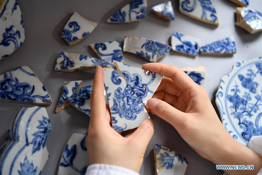 A porcelain restorer matches fragments of an ancient porcelain of Ming Dynasty in Jingdezhen, east China\'s Jiangxi Province, on Oct. 18, 2018. The National Cultural Heritage Administration will work out a plan to better protect cultural relics and speed up the creation of a safety oversight platform in 2019. Stressing the importance of such protection, Liu Yuzhu, head of the administration, said lax enforcement is a prominent problem that endangers cultural relics, at a meeting attended by cultural heritage administrators nationwide. (Xinhua/Wan Xiang)
