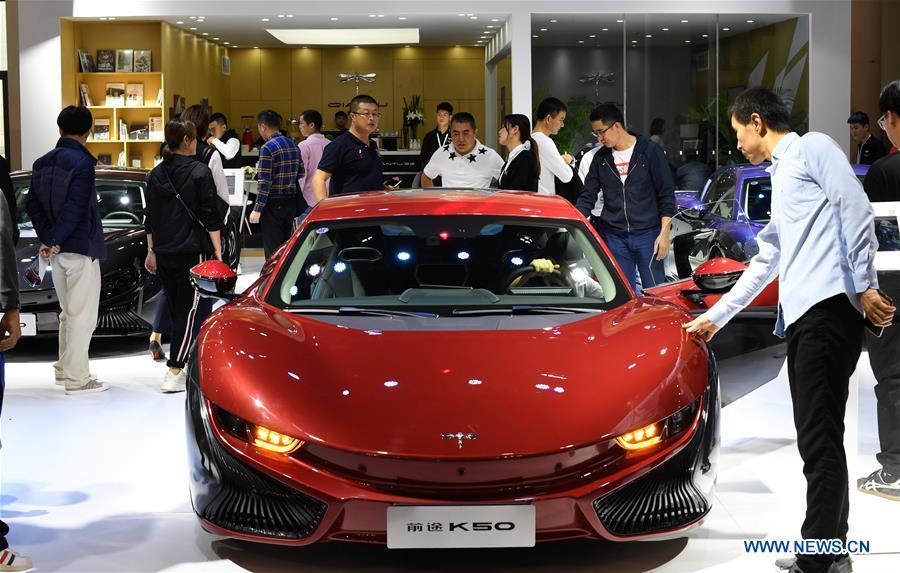 Visitors view a car from Chinese electric automaker Qiantu at Haikou New Energy Vehicle Exhibition in Haikou, south China\'s Hainan Province, Jan. 10, 2019. A total of 197 new energy vehicles were displayed at the exhibition. (Xinhua/Yang Guanyu)