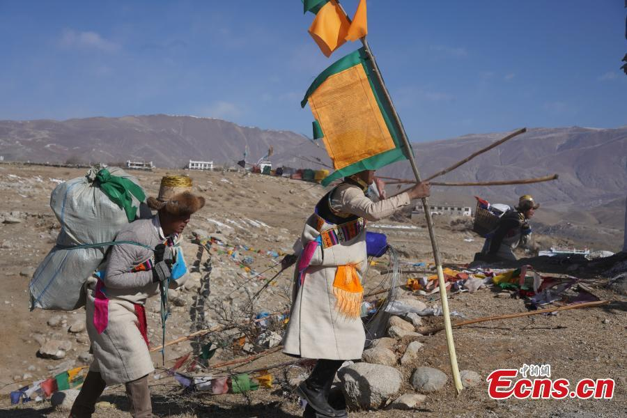 Tibetans hang prayer flags as part of celebrations for the New Year in the Tibetan calendar in Nyemo County, Southwest China\'s Tibet Autonomous region. In traditional highland barley farming areas, including Nyemo County, locals have a tradition of celebrating the Tibetan New Year one month early, so the celebrations do not affect farming. (Photo: China News Service/Sangdan Pingcuo)