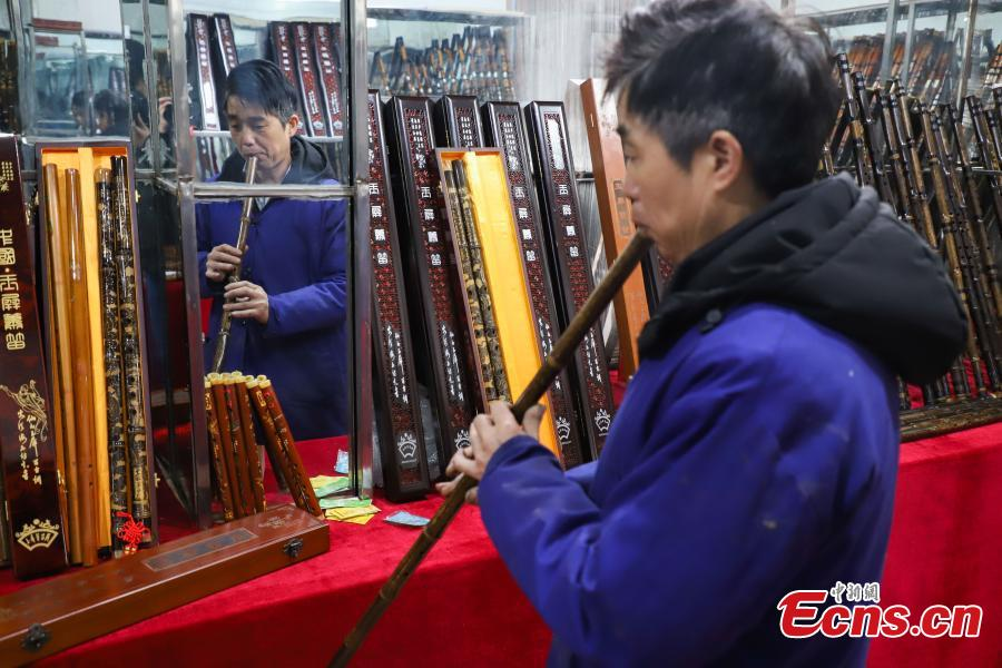 Wu Jihong, an inheritor of the Yuping bamboo flute-making craft, tunes a flute he made in Yuping Dong Autonomous County, Southwest China\'s Guizhou Province, Jan. 10, 2019. As a traditional Chinese bamboo instrument, the Yuping bamboo flute is famous for its clear tone and delicate carving. Made from local bamboo, the flute undergoes dozens of procedures before it is finished and merges folk cultures of several ethnic groups. It was listed as one of the National Intangible Cultural Heritages in 2006. (Photo: China News Service/Qu Honglun)
