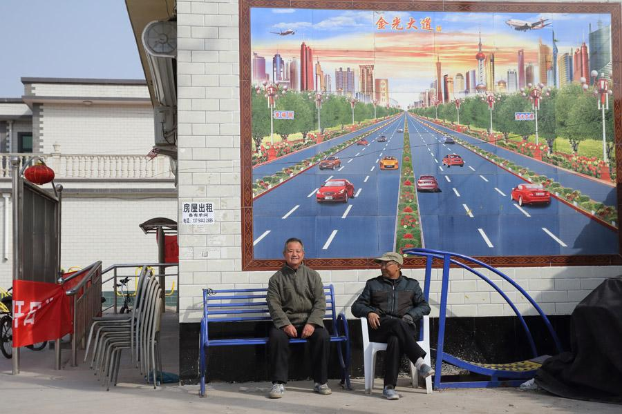Two villagers rest in front of a tile billboard in Baita village, Rongcheng county, Xiongan New Area, on March 29, 2018. (Photo by Wang Jing/China Daily)