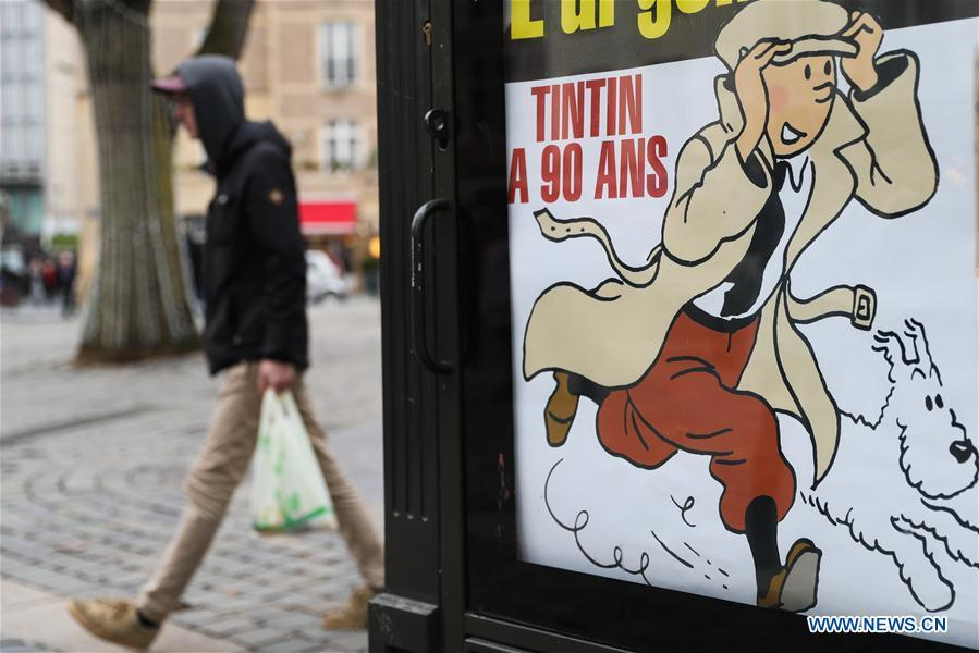 A man walks by a poster celebrating the 90th anniversary of \