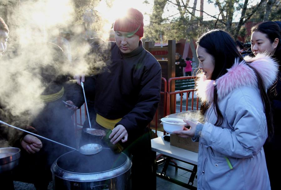 Volunteers serve freshly cooked Laba porridge at Yonghe Temple, Beijing, on Jan. 13, 2019. (Photo/China Daily)  Citizens and tourists gathered at Yonghe Temple in Beijing to receive Laba porridge on Sunday.  It was the eighth day of the 12th month of the Chinese lunar calendar, and Yonghe Temple opened to the public free of charge and distributed the porridge to mark the occasion.  Many people braved the cold weather to \