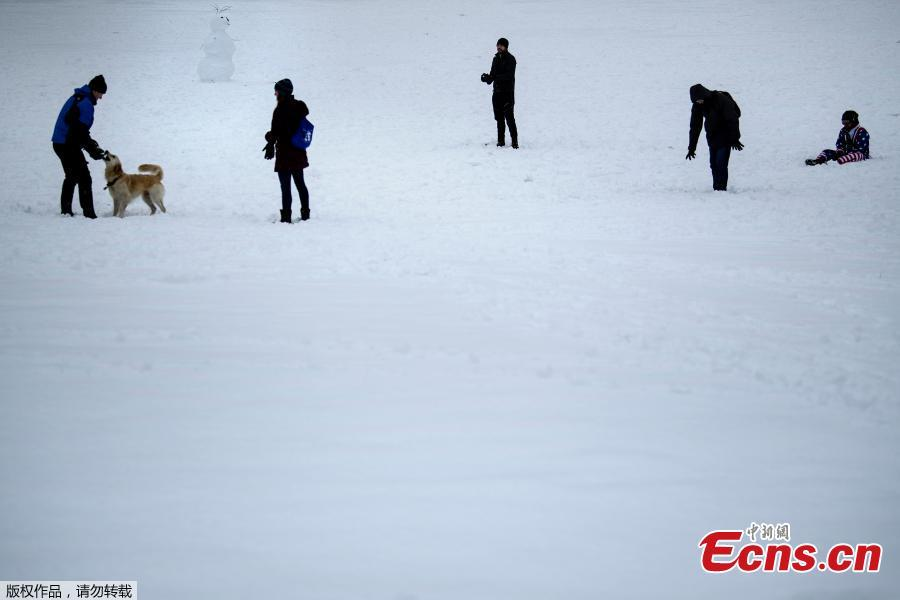 Visitors make their way through snow left by Winter Storm Gia, which paralyzed much of the midsection of the U.S., on the grounds of the Washington Monument, in Washington, DC, Jan. 13, 2019.  (Photo/Agencies)