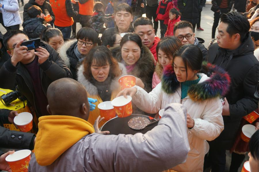 Visitors share Laba congee handed out for free during an event taking place in front of the temple\'s Shaolin Medicine health unit, Jan. 13, 2019. The congee was cooked according to a traditional recipe and included five types of beans as well as more than 20 minor ingredients. Buddhist temples across China have started handing out free Laba congee, a special meal served during the Laba Festival, which falls on the eighth day of the 12th lunar month and ushers in China\'s Lunar New Year celebrations. (Photo: China News Service/Han Zhangyun)