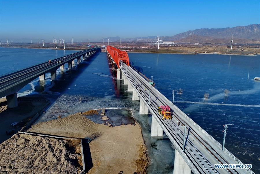 Aerial photo taken on Jan. 13, 2019 shows workers laying the tracks for the Beijing-Zhangjiakou high-speed railway line at Guanting Reservoir grand bridge in north China\'s Hebei Province. Track laying work of the Beijing-Zhangjiakou high-speed railway line at Guanting Reservoir grand bridge was completed on Sunday. The 174-km-long railway, connecting China\'s capital Beijing and Zhangjiakou of north China\'s Hebei Province, is a major transportation project for the 2022 Winter Olympic Games. (Xinhua/Yang Shiyao)