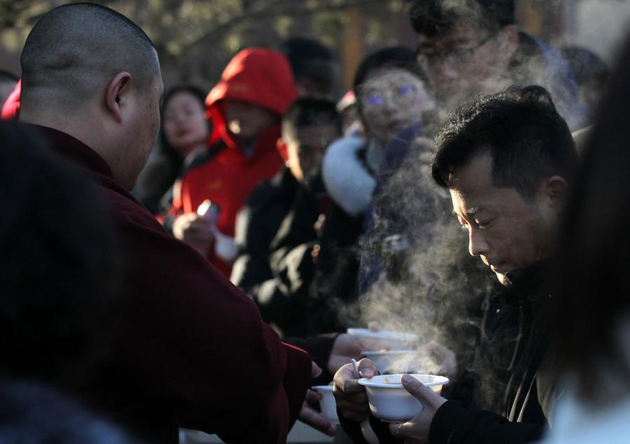 Visitors and tourists taste Laba porridge at Yonghe Temple, Beijing, on Jan. 13, 2019.  (Photo/China Daily)