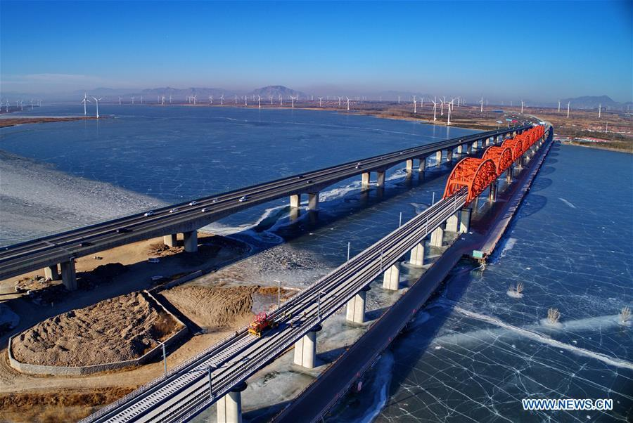 Aerial photo taken on Jan. 13, 2019 shows workers lay the tracks for the Beijing-Zhangjiakou high-speed railway line at Guanting Reservoir grand bridge in north China\'s Hebei Province. Track laying work of the Beijing-Zhangjiakou high-speed railway line at Guanting Reservoir grand bridge was completed on Sunday. The 174-km-long railway, connecting China\'s capital Beijing and Zhangjiakou of north China\'s Hebei Province, is a major transportation project for the 2022 Winter Olympic Games. (Xinhua/Yang Shiyao)