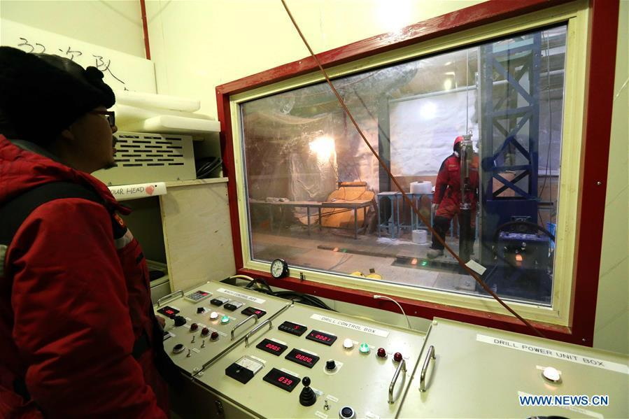 Fan Xiaopeng (L), a member of one of two inland expedition teams on China\'s 35th Antarctic expedition, operates the drilling equipment at the Kunlun Station in Antarctica, Jan. 12, 2019. (Xinhua/Liu Shiping)
