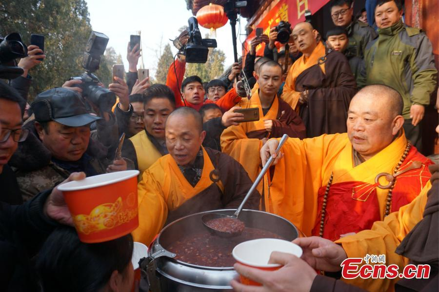 Shi Yongxin, the abbot at the Shaolin Temple, hands out Laba congee to visitors from across the country at an event taking place in front of the temple\'s Shaolin Medicine health unit, Jan. 13, 2019. The congee was cooked according to a traditional recipe and included five types of beans as well as more than 20 minor ingredients. Buddhist temples across China have started handing out free Laba congee, a special meal served during the Laba Festival, which falls on the eighth day of the 12th lunar month and ushers in China\'s Lunar New Year celebrations. (Photo: China News Service/Han Zhangyun)