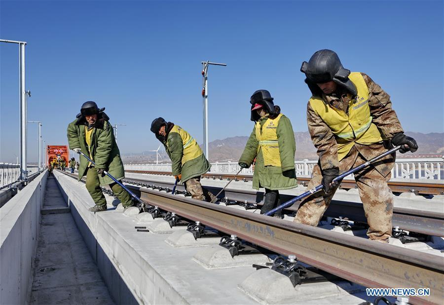 Workers lay the tracks for the Beijing-Zhangjiakou high-speed railway line at Guanting Reservoir grand bridge in north China\'s Hebei Province, on Jan. 13, 2019. Track laying work of the Beijing-Zhangjiakou high-speed railway line at Guanting Reservoir grand bridge was completed on Sunday. The 174-km-long railway, connecting China\'s capital Beijing and Zhangjiakou of north China\'s Hebei Province, is a major transportation project for the 2022 Winter Olympic Games. (Xinhua/Yang Shiyao)
