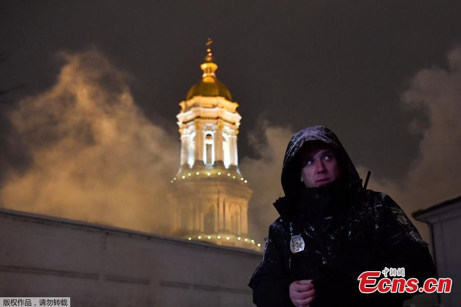 A policeman stands guard as firefighters try to extinguish a fire in one of the historic building of Kiev Pechersk Lavra, an historic Orthodox Christian monastery in the Ukrainian capital of Kiev on Jan. 14, 2019. According to the State Emergency Service\'s Kiev Department, there are no victims. Since its foundation, the Lavra has been a preeminent center of Eastern Orthodox Christianity in Eastern Europe and is one of the first to establish monasteries of Kievan Rus. (Photo/Agencies)
