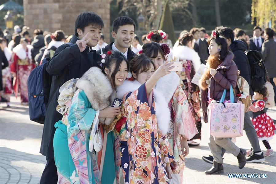 Japanese boys and girls take selfies to celebrate Coming of Age together at Tokyo Disneyland in Chiba, Japan, Jan. 14, 2019. People who turned 20-year-old took part in the annual Coming of Age Day ceremony in Japan on Monday. (Xinhua/Du Xiaoyi)