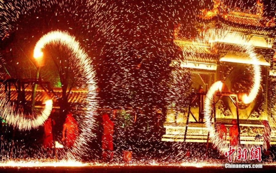 People perform a fire dragon dance in a shower of molten iron sparkling like fireworks to welcome the Spring Festival in Taierzhuang ancient town in Zaozhuang City, East China\'s Shandong Province, Jan. 13, 2019. The Spring Festival, or Chinese Lunar New Year, falls on Feb. 5 this year.  (Photo: China News Service/Yong Jun)