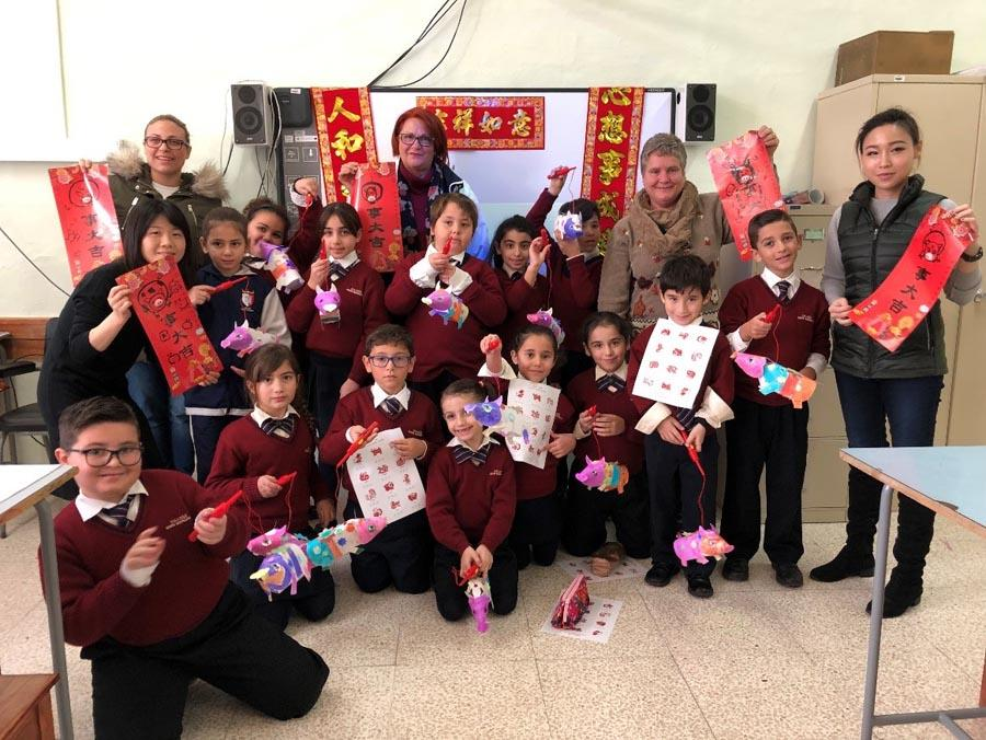 Students make pig-themed paper art at a primary school in Kalkara, Malta, on Jan. 10, 2019. (Photo/Chinaculture.org)