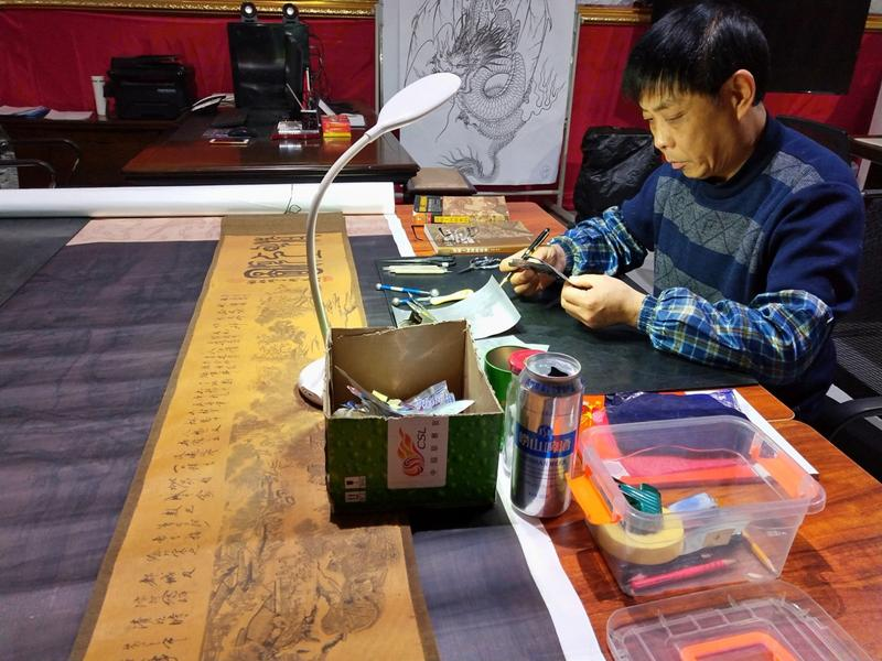 Gao Baoan works on his can-made replica of Riverside Scene at Qingming Festival. (Photo provided to chinadaily.com.cn)