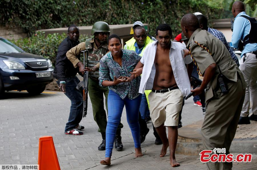 Security forces help civilians flee the scene as cars burn behind, at a hotel complex in Nairobi, Kenya Tuesday, Jan. 15, 2019. Terrorists attacked an upscale hotel complex in Kenya\'s capital Tuesday, sending people fleeing in panic as explosions and heavy gunfire reverberated through the neighborhood.  (Photo/Agencies)