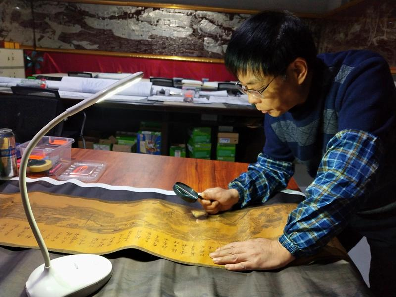 Gao Baoan studies a replica of the painting Riverside Scene at Qingming Festival.  (Photo provided to chinadaily.com.cn)