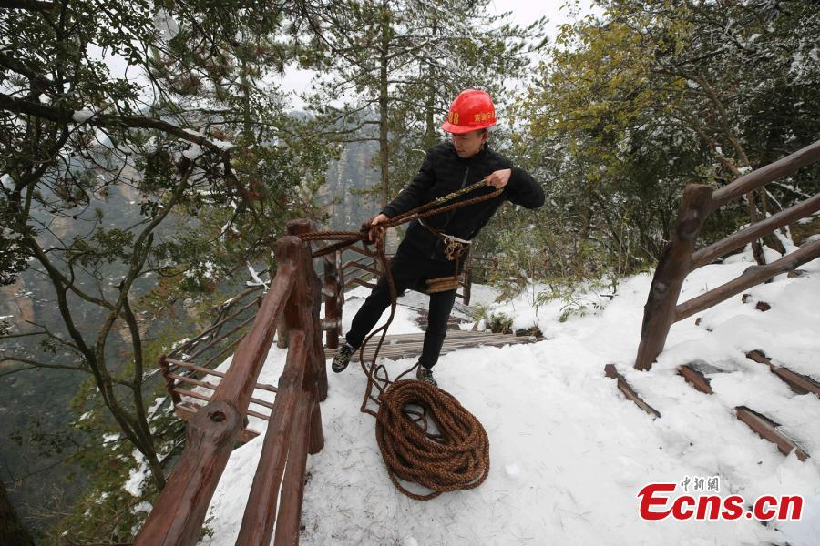 Su Songyun braves the winter cold to abseil down a cliff face and collect rubbish at the Huangshizhai scenic area in Zhangjiajie City, Central China\'s Hunan Province, Jan. 15, 2019. The 34-year-old local farmer began learning the stunt from his father in 2005, and his daredevil antics entertain tourists and enable him to collect garbage otherwise inaccessible on the mountain slope. (Photo: China News Service/Wu Yongbing)