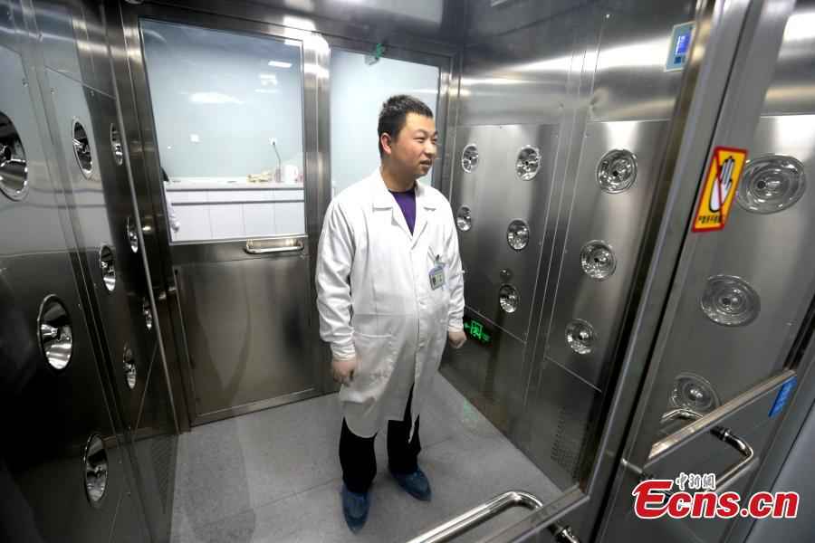A specialist goes through a series of checks before entering a room where relics undergo restoration at the Shaanxi History Museum in Xi\'an, Northwest China\'s Shaanxi Province, Jan. 16, 2019. Visitors can view the process through a glass window. (Photo: China News Service/Zhang Yuan)
