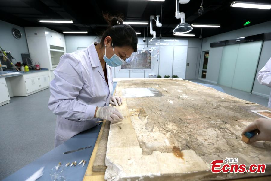 An ancient mural undergoes restoration work in a room at the Shaanxi History Museum in Xi\'an, Northwest China\'s Shaanxi Province, Jan. 16, 2019. Visitors can view the process through a glass window. (Photo: China News Service/Zhang Yuan)