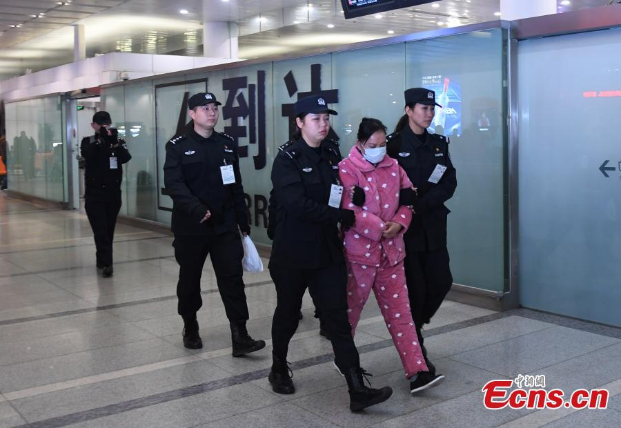 A Chinese woman suspected of illegal absorption of public deposits is escorted by police upon arrival at the Xiaoshan International Airport, Hangzhou City, Zhejiang Province, Jan. 16, 2019. The woman, the legal representative of a Hangzhou-based investment firm, was repatriated from Thailand on Wednesday. (Photo: China News Service/Wang Gang)