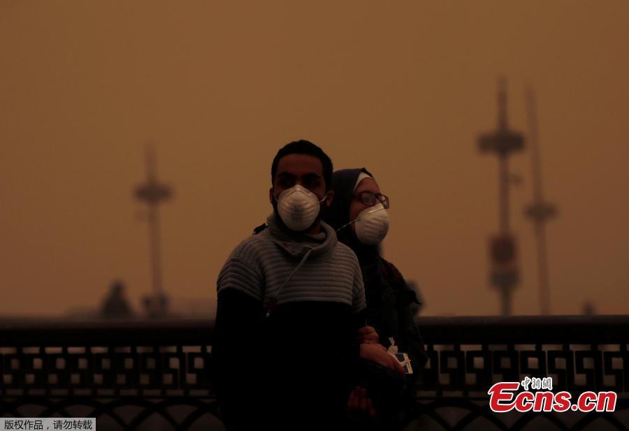 A couple covers their faces with masks during a sandstorm in Cairo, Egypt, Jan. 16, 2019. Egypt\'s capital Cairo and some of its port cities were hit by a severe sandstorm, with strong winds and heavy dust forcing the closure of several ports. (Photo/Agencies)